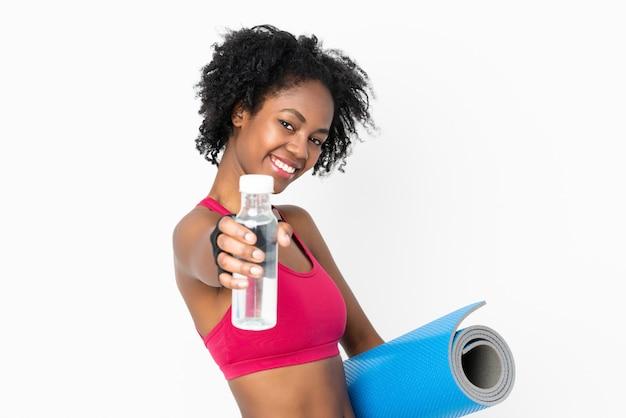 Giovane donna afroamericana sul muro bianco con bottiglia d'acqua sport e con una stuoia