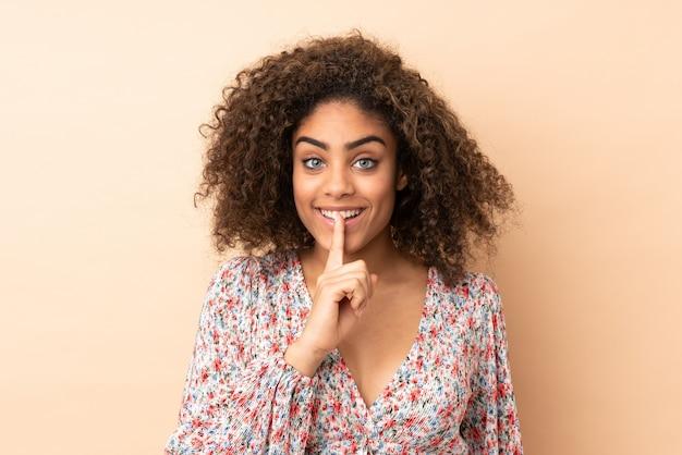 Giovane donna afroamericana sulla parete beige che mostra un segno di gesto di silenzio che mette il dito in bocca