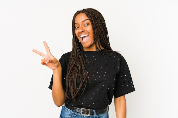 Giovane donna afroamericana sulla parete bianca allegra e spensierata mostrando un simbolo di pace con le dita.
