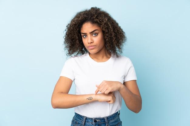 Giovane donna afroamericana sulla parete blu che fa il gesto di essere in ritardo