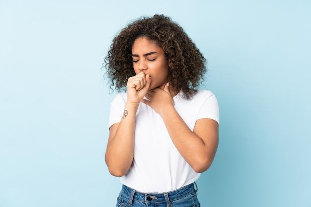 Giovane donna afroamericana sulla parete blu che tossisce molto
