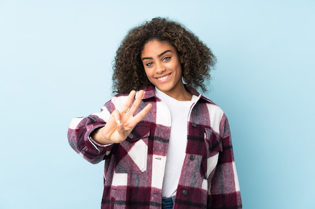 Giovane donna afroamericana sulla parete blu felice e contando tre con le dita
