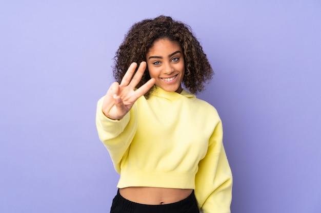 Giovane donna afroamericana sulla parete felice e contando tre con le dita
