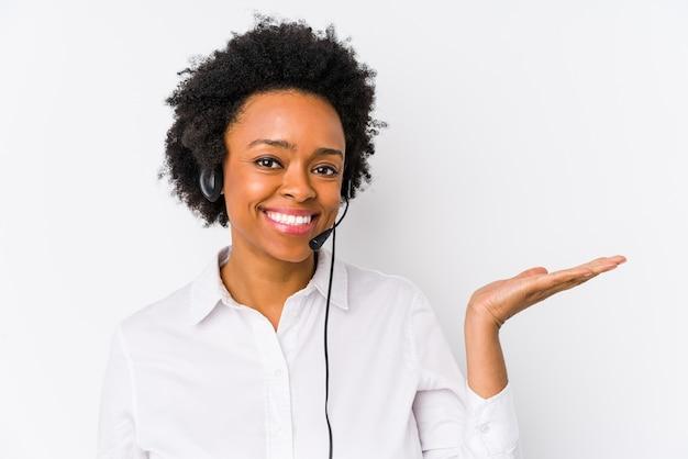 Giovane donna afroamericana telemarketer isolata mostrando uno spazio di copia su un palmo e tenendo un'altra mano sulla vita.