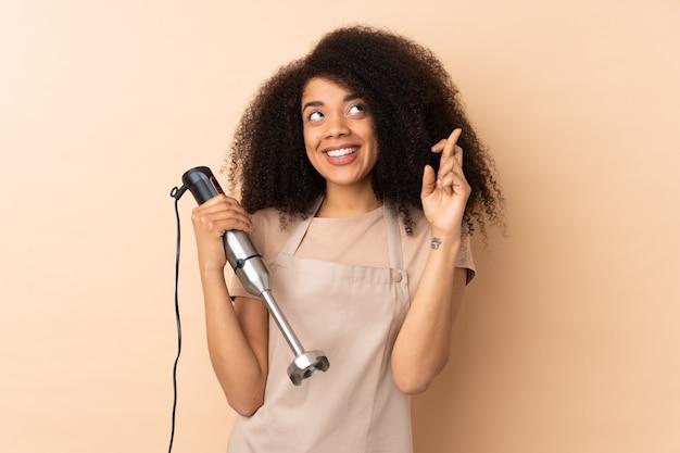 Giovane donna afroamericana utilizzando frullatore a immersione isolato su beige con le dita che attraversano