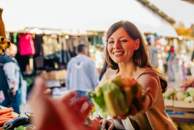 Giovane donna al mercato scegliendo verdure.