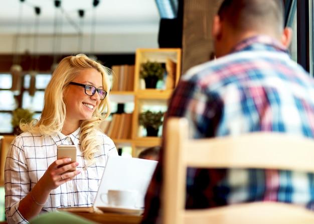 Giovane donna al messaggio di battitura a macchina della barra del caffè al telefono cellulare.