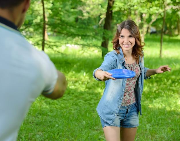 Giovane donna all'aperto gettando un frisbee nel parco