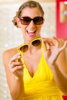 Giovane donna all'ottico con gli occhiali da sole