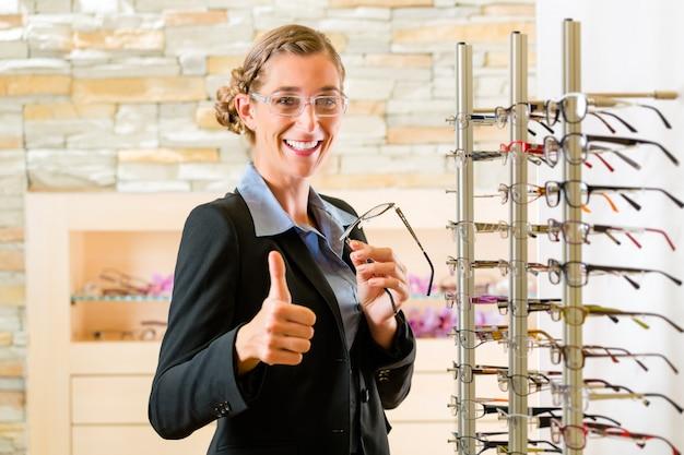 Giovane donna all'ottico con gli occhiali, potrebbe essere cliente o commesso