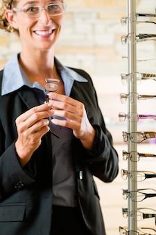 Giovane donna all'ottico con gli occhiali, potrebbe essere cliente o venditore