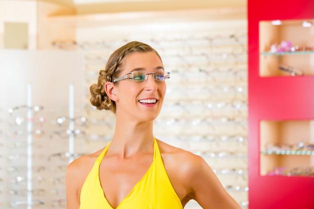 Giovane donna all'ottico con gli occhiali
