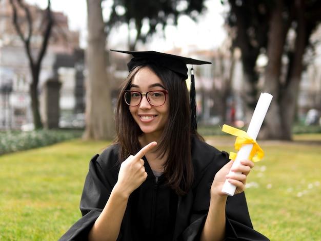 Giovane donna alla cerimonia di laurea all'aperto