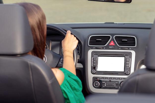 Giovane donna alla guida di un'auto in città.