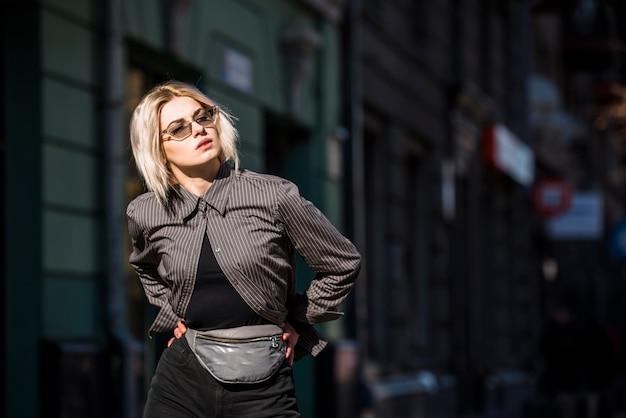 Giovane donna alla moda bionda con la mano sulle anche che distolgono lo sguardo