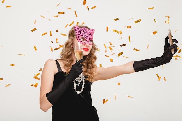 Giovane donna alla moda che beve champagne, facendo foto di auto