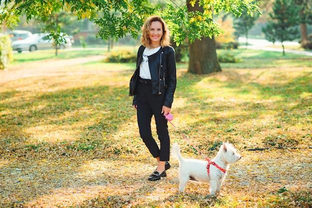 Giovane donna alla moda che cammina con il suo piccolo terrier bianco di altopiano ad ovest in un parco. migliori amici.