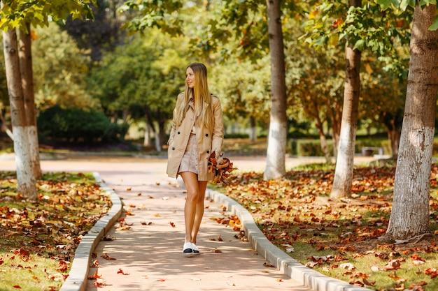 Giovane donna alla moda che cammina nel parco autunnale