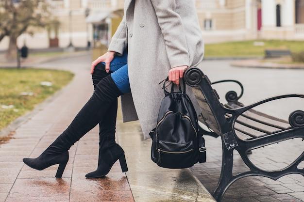 Giovane donna alla moda che cammina nella città d'autunno, stagione fredda, indossa stivali neri con i tacchi alti, zaino in pelle, accessori, cappotto grigio, seduto sulla panchina, tendenza della moda, dettagli del primo piano delle gambe