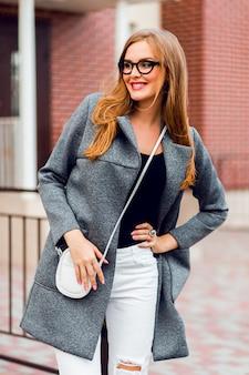 Giovane donna alla moda che cammina sulla strada alla bella giornata di sole autunnale, indossando cappotto vintage e occhiali da sole.