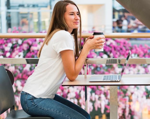 Giovane donna alla moda che gode del caffè