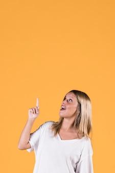 Giovane donna alla moda che indica direzione verso l'alto con la bocca aperta