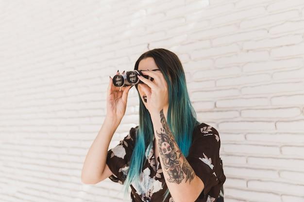 Giovane donna alla moda che osserva attraverso il binocolo contro la parete