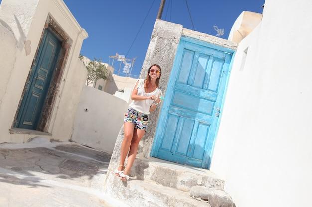 Giovane donna alla moda che parla sul telefono e che sta vicino alla porta blu nel villaggio greco di emporio