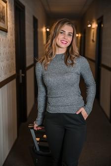 Giovane donna alla moda che posa con la valigia che sta nel corridoio dell'hotel