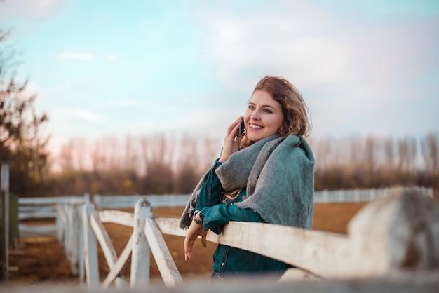 Giovane donna alla moda che si appoggia recinzione e che parla sul telefono.