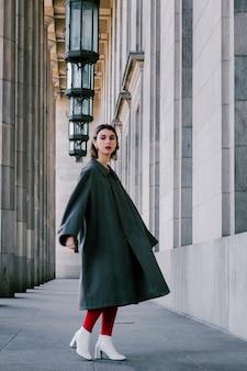 Giovane donna alla moda che si leva in piedi sotto la riga dell'apparecchiatura accesa