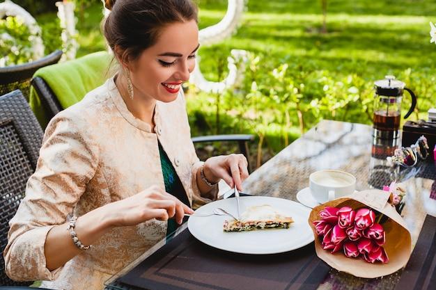 Giovane donna alla moda che si siede nella caffetteria, mangiando una gustosa torta