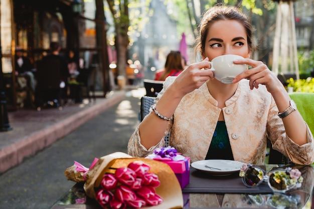Giovane donna alla moda che si siede nella caffetteria, tenendo la tazza di cappuccino