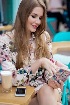 Giovane donna alla moda che si siede nella caffetteria