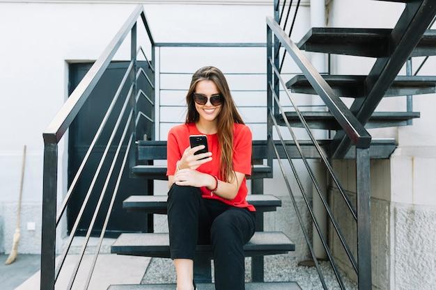 Giovane donna alla moda che si siede sulla scala usando smartphone