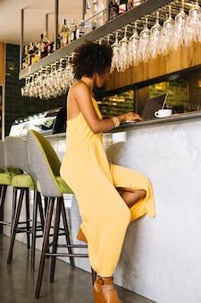 Giovane donna alla moda che si siede vicino al contatore della barra facendo uso del computer portatile