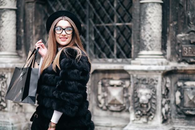 Giovane donna alla moda con i sacchetti della spesa in mani che posano sui precedenti dell'architettura di vecchia città