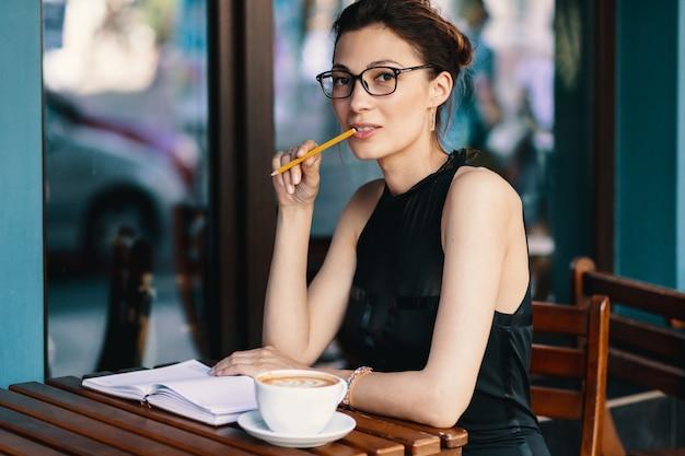 Giovane donna alla moda con i vetri alla moda che si siedono alla tavola