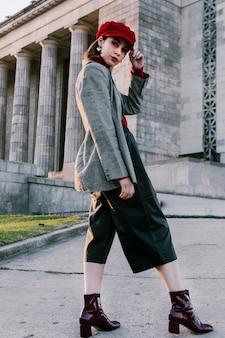 Giovane donna alla moda con la mano sul suo berretto rosso che guarda l'obbiettivo