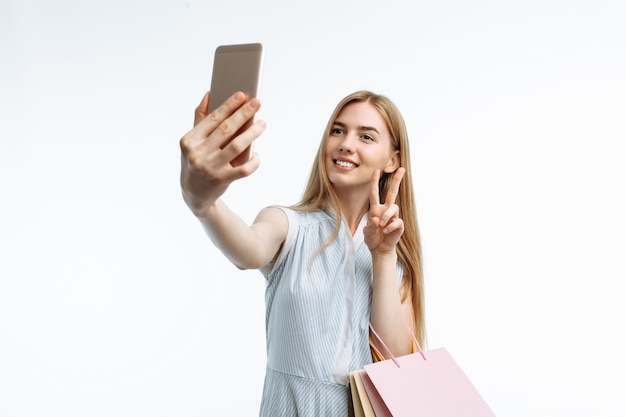 Giovane donna alla moda, con sacchetti regalo, in posa e prendendo un selfie al telefono con i sacchetti di shopping