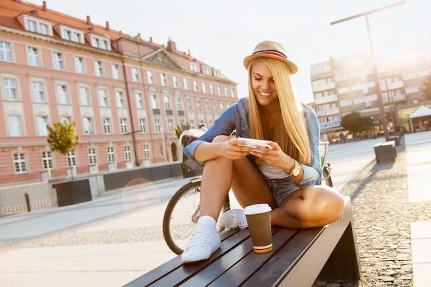 Giovane donna alla moda con una bicicletta