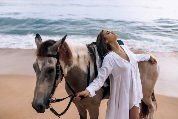 Giovane donna alla moda felice in un vestito bianco che posa con un cavallo sulla spiaggia.