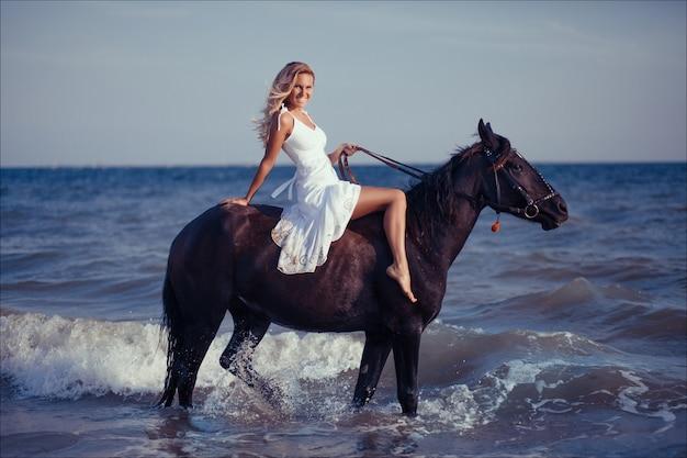 Giovane donna alla moda felice in vestito bianco che posa con un cavallo sulla spiaggia dell'oceano