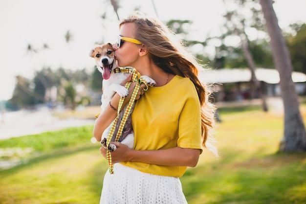 Giovane donna alla moda hipster che tiene camminare giocando cucciolo di cane jack russell, parco tropicale, sorridente e divertirsi, vacanze, occhiali da sole, berretto, camicia gialla, spiaggia di sabbia