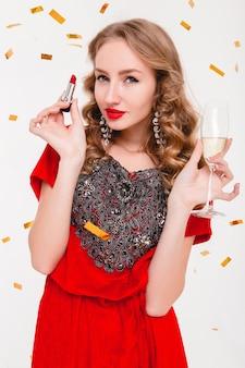 Giovane donna alla moda in abito da sera rosso che celebra il nuovo anno che tiene rossetto rosso e bicchiere di champagne