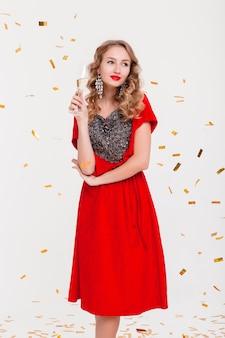 Giovane donna alla moda in abito da sera rosso che celebra il nuovo anno, tenendo in mano un bicchiere di champagne