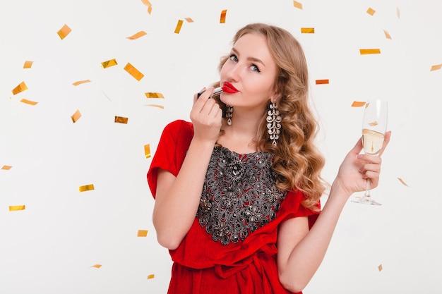 Giovane donna alla moda in abito da sera rosso che celebra il nuovo anno utilizzando rossetto rosso e tenendo un bicchiere di champagne