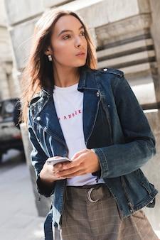 Giovane donna alla moda in giacca di jeans utilizzando smartphone