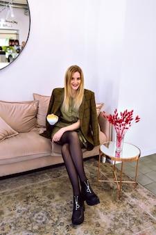 Giovane donna alla moda in posa al moderno caffè hipster, indossando abiti eleganti e bevendo il suo caffè mattutino, atmosfera europea.