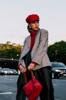 Giovane donna alla moda in protezione rossa che propone sulla borsa della holding della strada